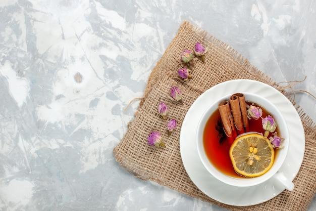 Widok z góry na filiżankę herbaty z cynamonem i cytryną na białej powierzchni