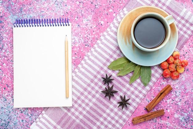 Widok z góry na filiżankę herbaty z cynamonowym notatnikiem i wiśniami na różowym backgruond herbata napój owocowy kolor
