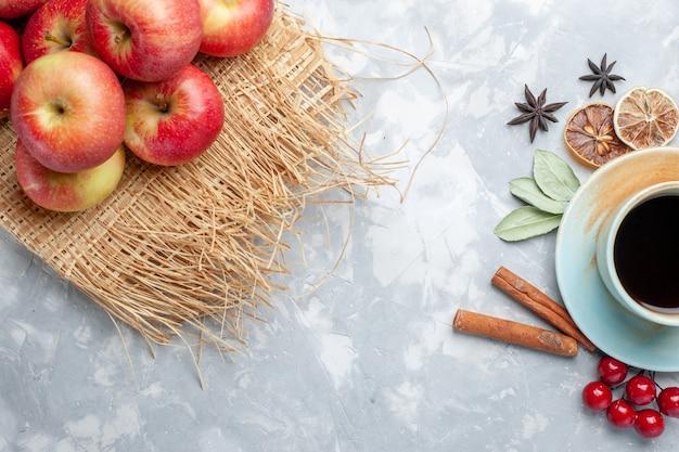 Widok z góry na filiżankę herbaty z cynamonowymi czerwonymi jabłkami i suszonymi plasterkami cytryny na lekkim biurku herbata cukierki kolor owoców
