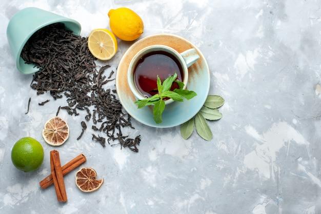Widok z góry na filiżankę herbaty z cytryną i cynamonem na jasnym stole, suszone owoce cytrusowe zbożowe