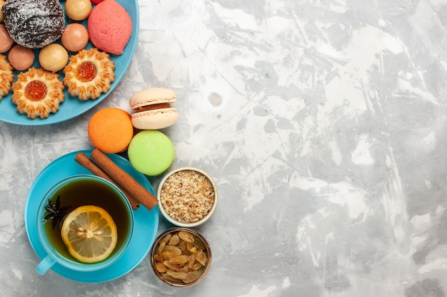 Widok z góry na filiżankę herbaty z francuskimi ciasteczkami cukrowymi macarons i ciastami na białej powierzchni