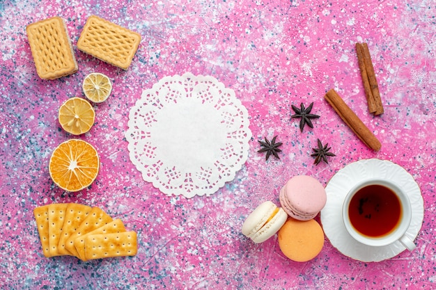 Widok z góry na filiżankę herbaty z francuskimi makaronikami i krakersami na różowym biurku