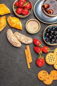 Widok z góry na filiżankę herbaty z herbatnikami i owocami na ciemnej powierzchni słodkie ciasteczko z owocami