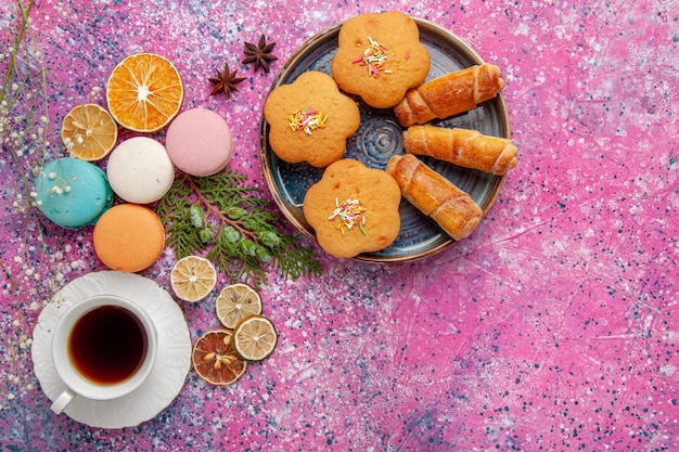 Widok z góry na filiżankę herbaty z kolorowymi francuskimi makaronikami i bajglami na jasnoróżowej ścianie ciasto biszkoptowo-cukrowe słodkie ciasto herbaciane ciastko
