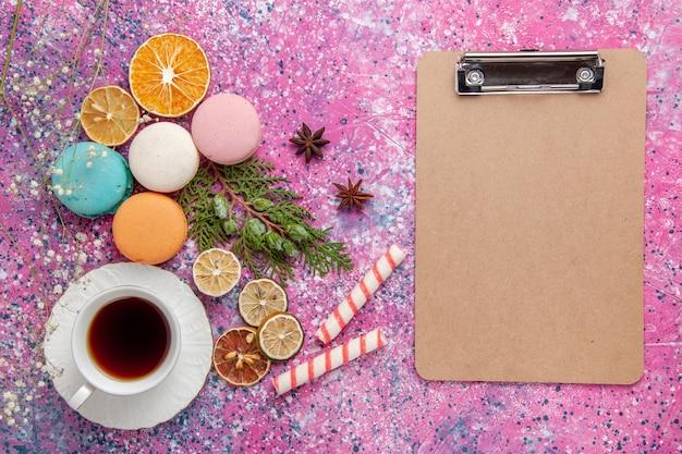 Widok z góry na filiżankę herbaty z kolorowymi francuskimi makaronikami i notatnikiem na różowej ścianie ciasto biszkoptowe cukier słodkie ciasto herbaciane ciasteczko
