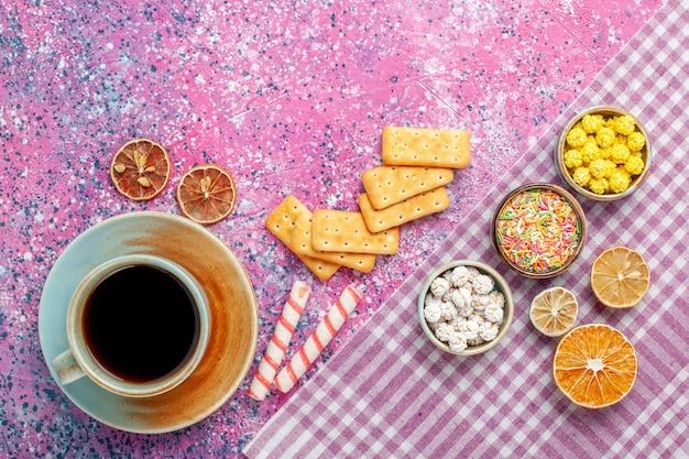 Widok z góry na filiżankę herbaty z krakersami i cukierkami na różowym biurku