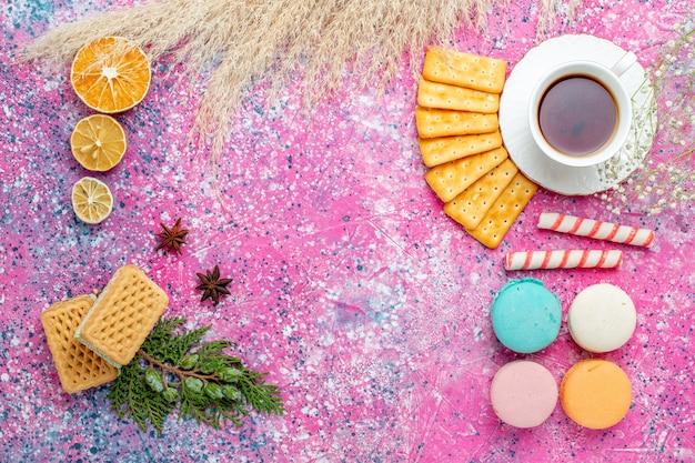 Widok z góry na filiżankę herbaty z krakersami i francuskimi makaronikami na jasnoróżowym biurku