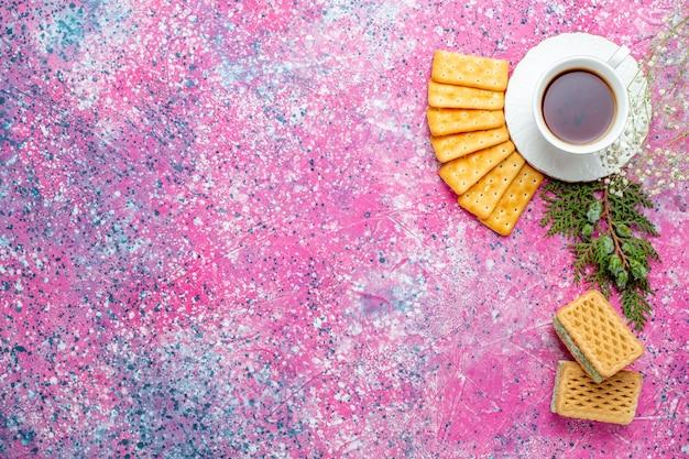 Widok z góry na filiżankę herbaty z krakersami i goframi na jasnoróżowym biurku