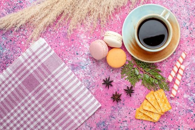 Widok z góry na filiżankę herbaty z krakersami i makaronikami na jasnoróżowym biurku