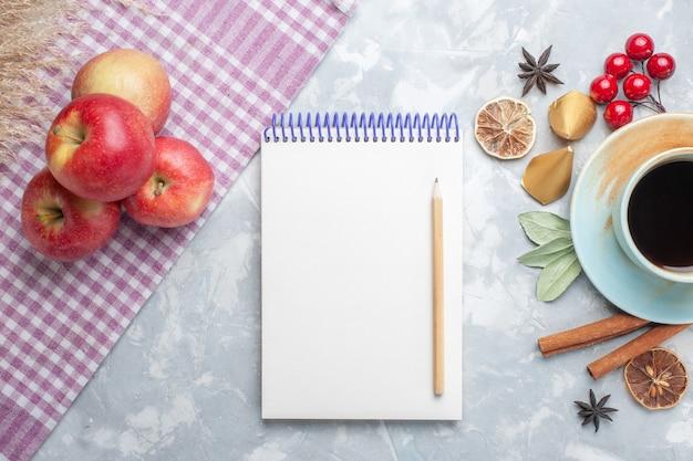 Widok z góry na filiżankę herbaty z notatnikiem z czerwonych jabłek cynamonu i suszonymi plasterkami cytryny na lekkim biurku herbata cukierki kolor śniadanie owoce