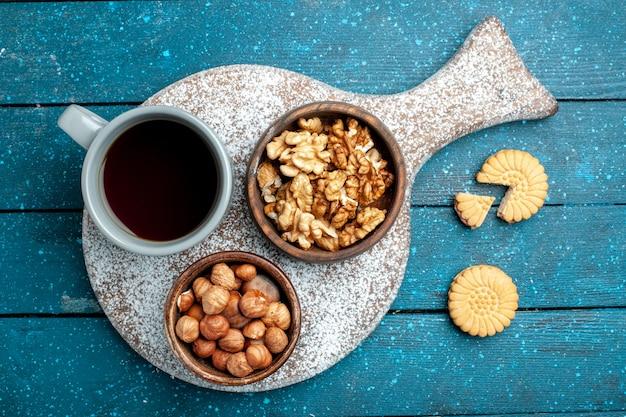 Widok z góry na filiżankę herbaty z orzechami włoskimi i orzechami laskowymi na niebiesko rustykalne biurko orzechowe w kolorze herbaty