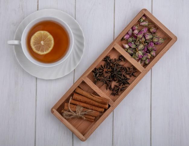 Widok z góry na filiżankę herbaty z plasterkiem cytryny i goździków cynamonowych i suszonych pąków róży na szarym tle