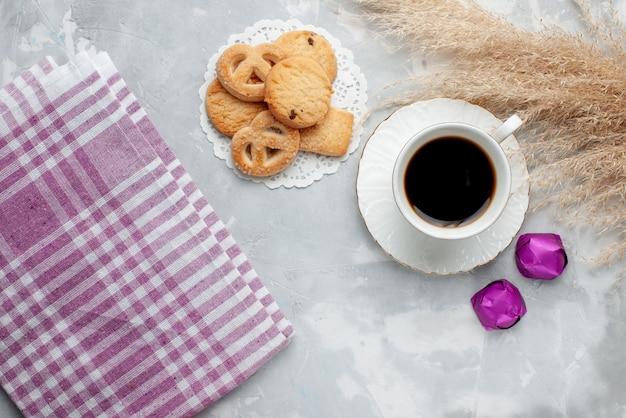 Widok z góry na filiżankę herbaty z pysznymi małymi ciasteczkami czekoladowymi cukierkami na lekkim, ciasteczkowym słodkim cukrze