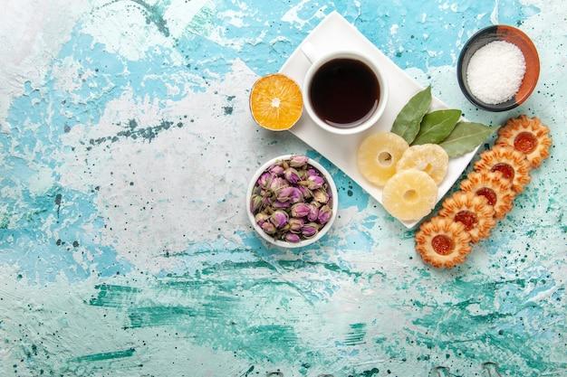 Widok z góry na filiżankę herbaty z suszonymi krążkami ananasa i ciasteczkami na jasnoniebieskiej powierzchni