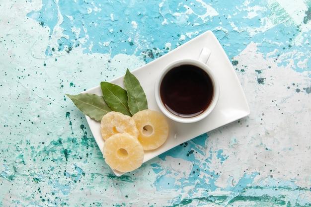 Widok z góry na filiżankę herbaty z suszonymi krążkami ananasa na jasnoniebieskiej powierzchni