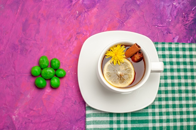 Widok z góry na filiżankę herbaty z zielonymi cukierkami na różowym cukierku w kolorze herbaty