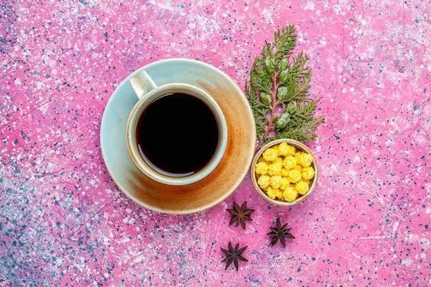Widok z góry na filiżankę herbaty z żółtymi cukierkami na różowym biurku
