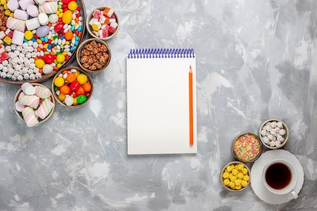 Widok z góry na filiżankę herbaty ze słodkimi konfiturami i notatnik na białym biurku