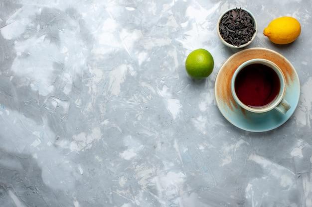 Widok z góry na filiżankę herbaty ze świeżymi cytrynami i suszoną herbatą na jasnym stole, herbaciany kolor cytrusowy