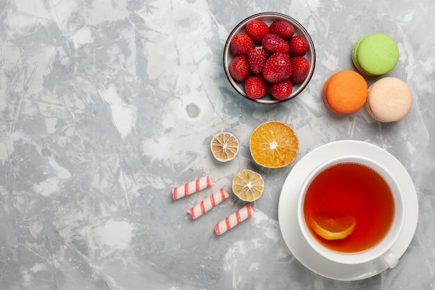 Widok z góry na filiżankę herbaty ze świeżymi czerwonymi truskawkami i francuskimi makaronikami na białej powierzchni
