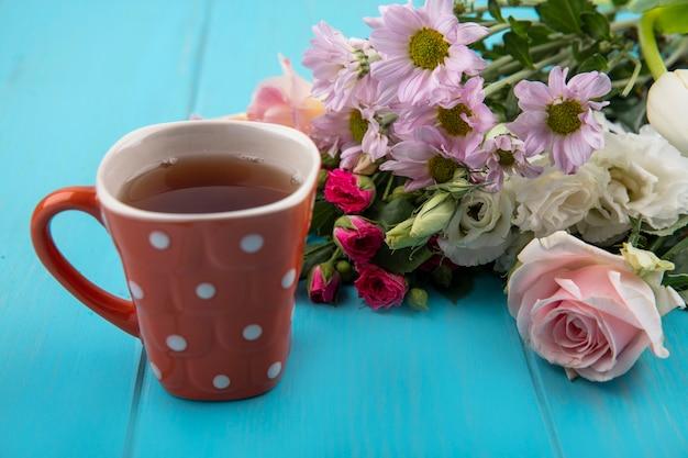 Widok z góry na filiżankę herbaty ze wspaniałymi świeżymi kwiatami na białym tle na niebieskim tle drewnianych