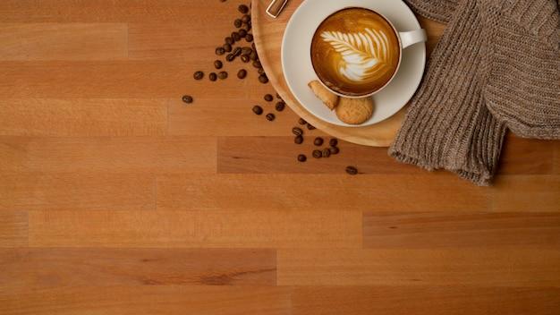 Widok z góry na filiżankę kawy i ciastka na drewnianym stole ozdobionym ziaren kawy i swetrem