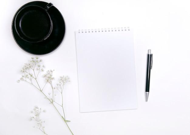 Widok z góry na filiżankę kawy i notatnik z kwiatami na białym tle