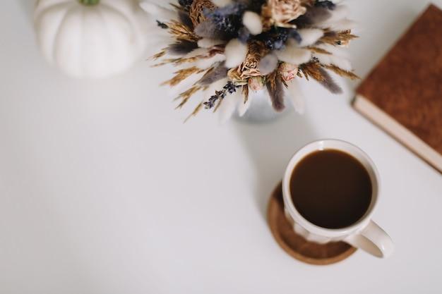 Widok z góry na filiżankę kawy i suszonych kwiatów na białym tle