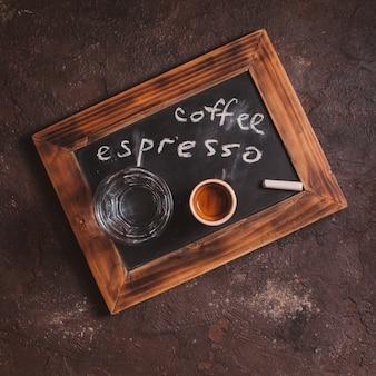 Widok z góry na filiżankę kawy i szklaną wodę na tabliczce ze starej szkoły z napisem