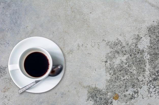 Widok z góry na filiżankę kawy na tle cementu