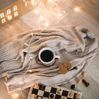Widok z góry na filiżankę kawy w beżową kratę i szachownicę hobby concept
