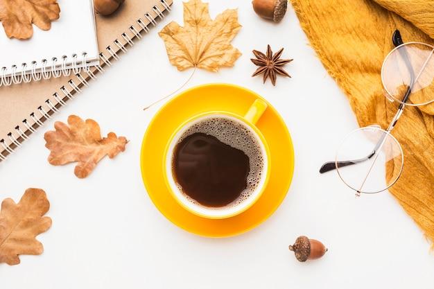 Widok z góry na filiżankę kawy w okularach i jesiennych liściach
