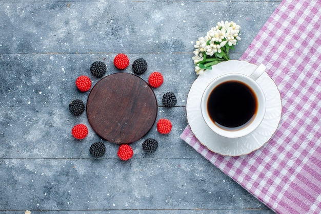 Widok z góry na filiżankę kawy wraz z jagodami konfitury na szarym, słodkim cieście do pieczenia ciasta z cukrem