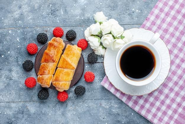 Widok z góry na filiżankę kawy wraz ze słodkimi pysznymi bransoletkami i jagodami na szarym, słodkim cukierniczym cieście do pieczenia