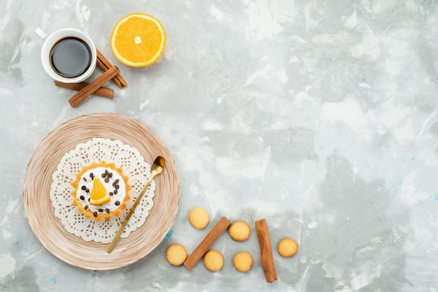 Widok z góry na filiżankę kawy z ciasteczkami cynamonowymi i kremowym ciastem na jasnej powierzchni słodkich owoców