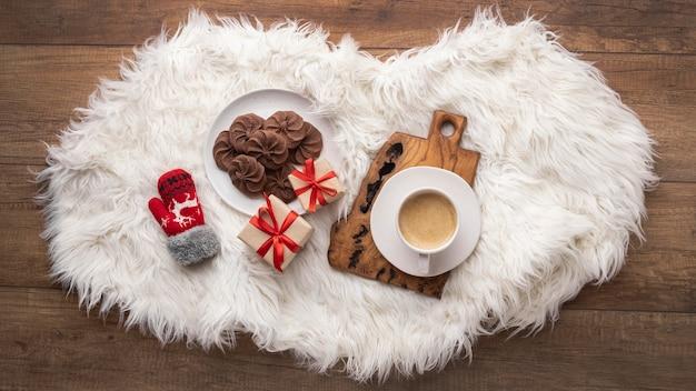Widok z góry na filiżankę kawy z ciasteczkami i prezentami