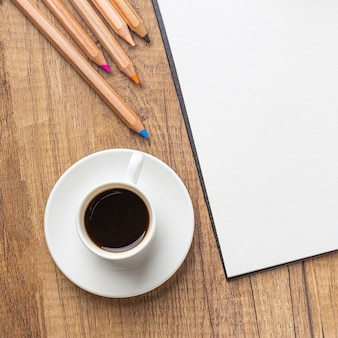 Widok z góry na filiżankę kawy z kolorowymi kredkami