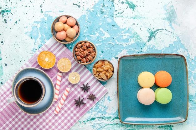Widok z góry na filiżankę kawy z rodzynkami francuskimi makaronikami i konfiturami na jasnoniebieskim cieście na biurku upiec słodkie ciastko cukrowe