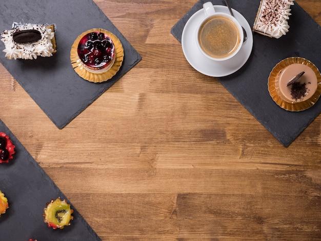Widok z góry na filiżankę kawy z różnymi ciastami o różnych smakach nad drewnianym stołem. ciasta z kremem budyniowym. ciasto z białą śmietaną i pysznym biszkoptem na wierzchu.