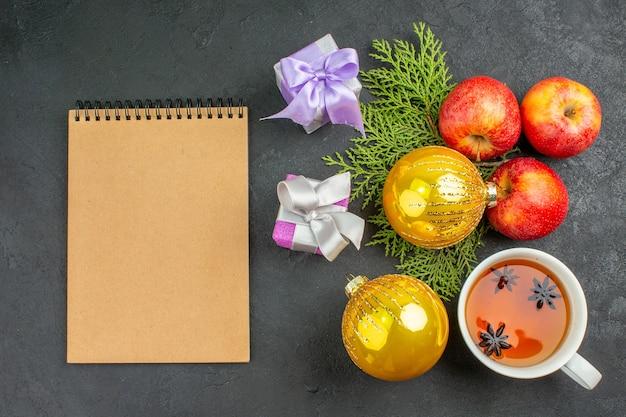 Widok z góry na filiżankę prezentów z czarnej herbaty i ekologiczne akcesoria do dekoracji świeżych jabłek i zeszyty na czarnym stole