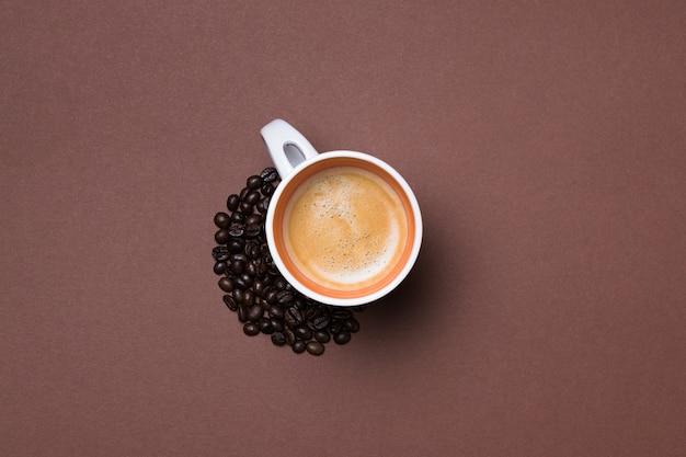 Widok z góry na filiżankę świeżego espresso otoczoną ziarnami kawy na brązowej powierzchni