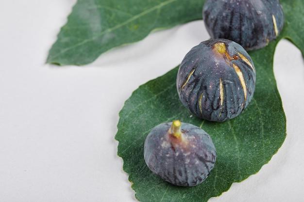 Widok z góry na fioletowe figi z liściem na białym tle.