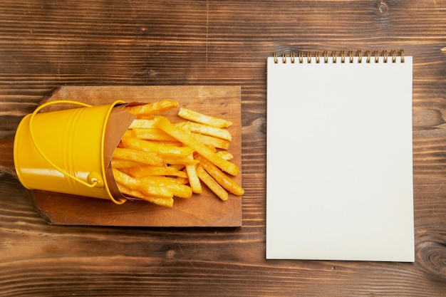 Widok z góry na frytki wewnątrz małego kosza z notatnikiem na brązowym stole