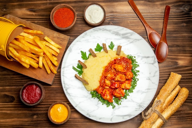 Widok z góry na frytki z plastrami kurczaka na brązowym stole