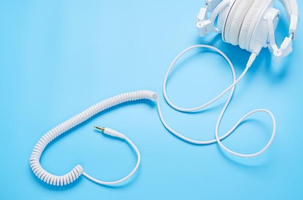 Widok z góry na gadżety na niebieskim tle, skład białych słuchawek i drutów w kształcie serca