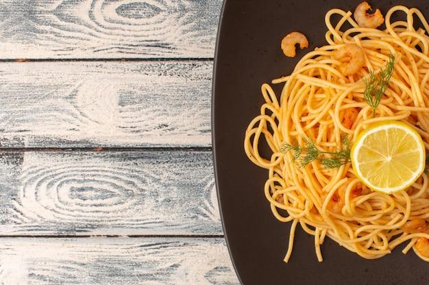Widok z góry na gotowany włoski makaron z zieleniną krewetek i cytryną wewnątrz brązowego talerza