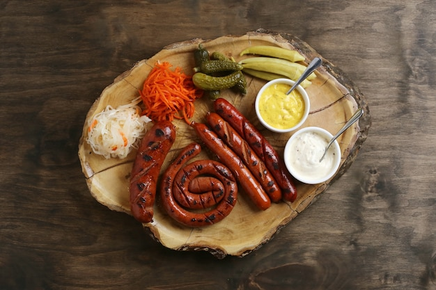 Widok z góry na grillowane kiełbaski z dodatkami i sosami