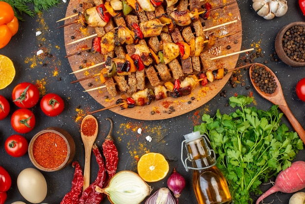 Widok z góry na grillowane szaszłyki z kurczaka na drewnianej desce i inne potrawy na stole?