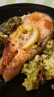 Widok z góry na grillowany stek z łososia podany na czarnym talerzu z dodatkami warzywnymi z brokułów - pionowo