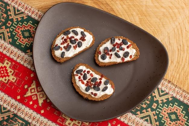 Widok z góry na grzanki z chleba wewnątrz ciemnego talerza na drewnianym stole